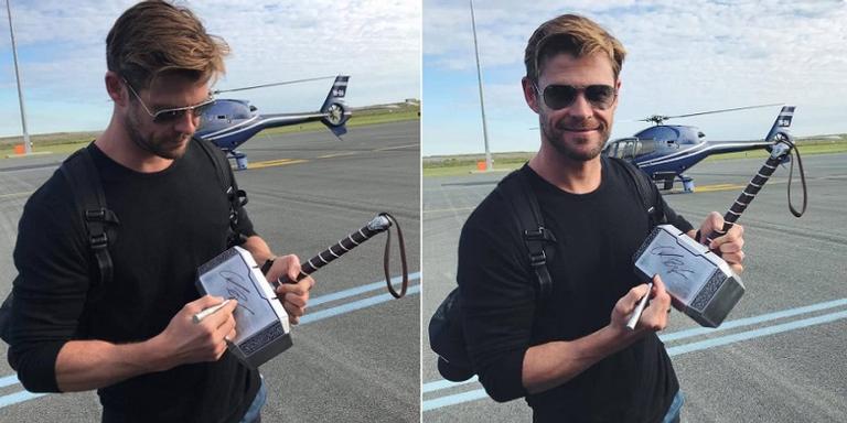 Chris Hemsworth autografa martelo do Thor para que o objeto seja leiloado.